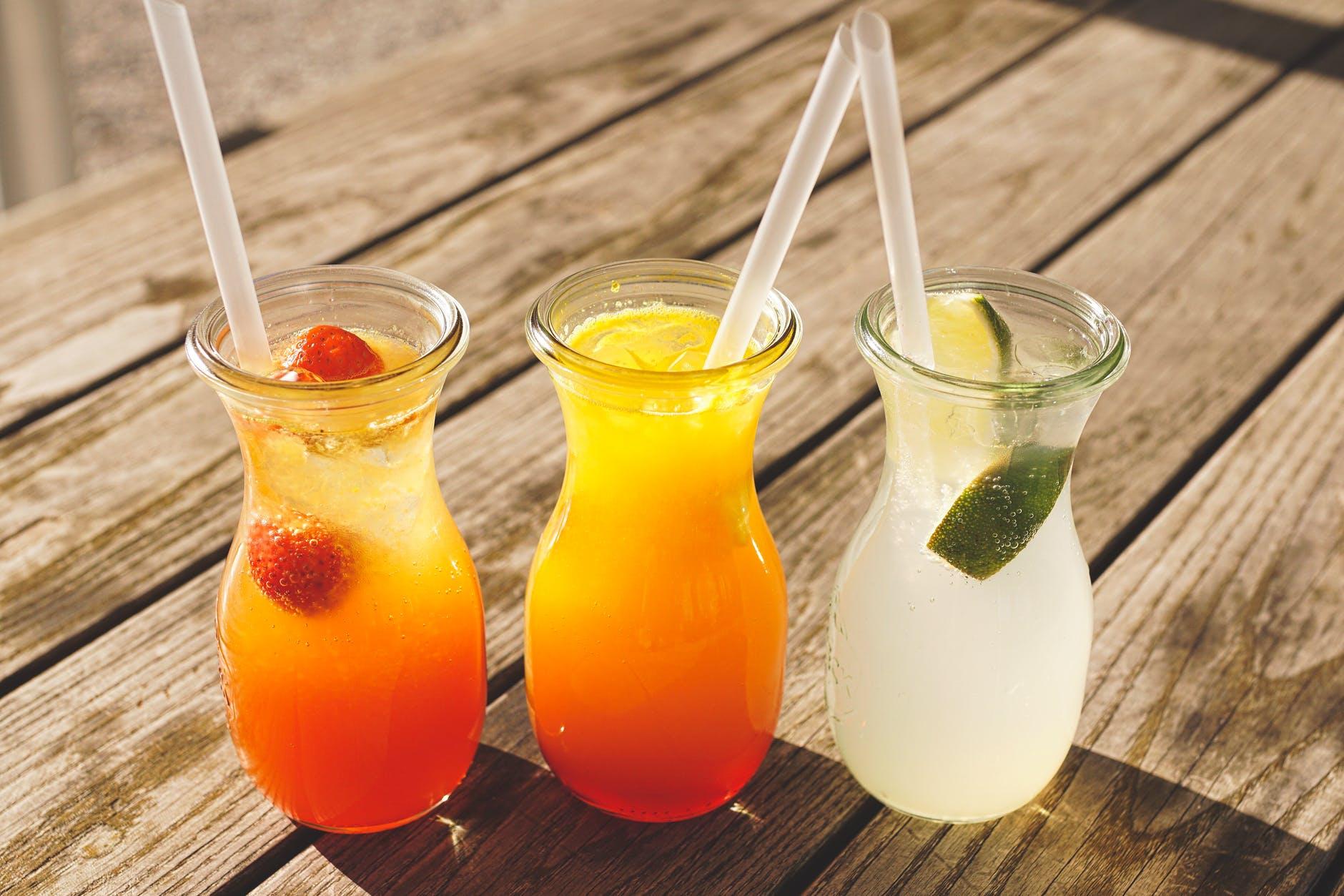 three assorted fruit juice in glasses